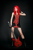 Fille rousse de culbuteur avec la guitare basse rouge Images libres de droits