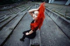 Fille rousse de style s'asseyant dessus dehors Femme avec la coiffure colorée vibrante tenant ses cheveux et regardant à l'appare Photographie stock libre de droits