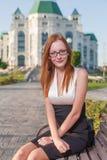 Fille rousse de style s'asseyant sur le banc photographie stock libre de droits