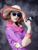 Fille rousse drôle dans le chapeau avec l'appareil-photo et bokeh au fond image stock