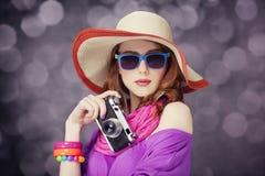 Fille rousse drôle dans le chapeau avec l'appareil-photo et bokeh au fond images stock