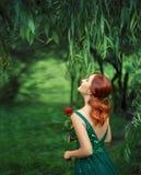 Fille rousse en vert, émeraude, robe luxueuse avec un dos nu recherchant et rire Photo du dos avec Images stock