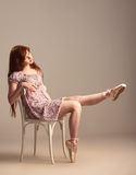 Fille rousse essayant sur des chaussures de pointe Image stock