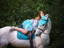 Fille rousse et cheval blanc dans la forêt Image libre de droits