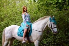 Fille rousse et cheval blanc dans la forêt Images stock