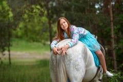Fille rousse et cheval blanc dans la forêt Photographie stock