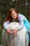 Fille rousse et cheval blanc dans la forêt Photo libre de droits