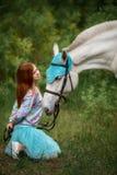 Fille rousse et cheval blanc dans la forêt Photos stock