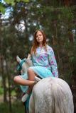 Fille rousse et cheval blanc dans la forêt Image stock