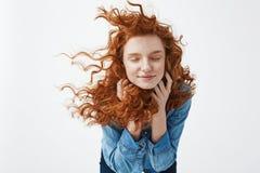 Fille rousse gaie attirante avec piloter rire de sourire de cheveux bouclés avec les yeux fermés au-dessus du fond blanc image libre de droits