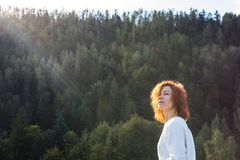Fille rousse mignonne appréciant le soleil dans la forêt image stock