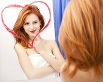 Fille rousse près de miroir Images stock