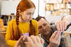 Fille rousse regardant le professeur sculptant l'argile photo libre de droits