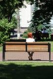 Fille rousse s'asseyant sur le banc en parc de ville et parlant au téléphone Image stock