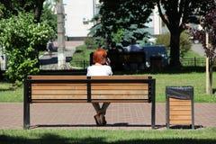 Fille rousse s'asseyant sur le banc en parc de ville et parlant au téléphone Photos libres de droits
