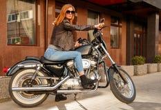 Fille rousse s'asseyant sur une moto Photo libre de droits