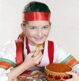 Fille russe avec le caviar et une crêpe dans un han Photographie stock libre de droits