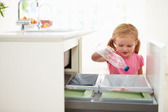 Fille réutilisant des déchets de cuisine dans la poubelle Images stock
