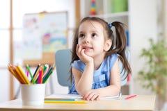 Fille rêveuse d'enfant avec des crayons au centre de soins de jour Images stock