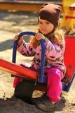Fille sérieuse d'enfant en bas âge sur la lèvre inférieure acérée de terrain de jeu photos libres de droits