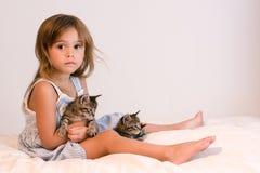 Fille sérieuse et mignonne tenant les chatons tigrés sur l'édredon blanc cassé mol Image stock