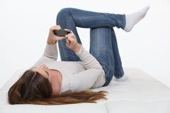 Fille s'étendant sur le film de observation arrière sur son mobile Image libre de droits