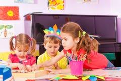 Fille s'étirant pour le papier dans la classe de jardin d'enfants Photos stock