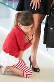 Fille s'accrochant à la jambe de la mère Photo stock