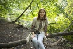 Fille s'asseyant à la branche d'arbre dans la forêt Photo libre de droits