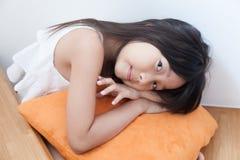 Fille s'asseyant étreignant l'orange d'oreiller Image stock