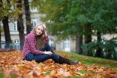 Fille s'asseyant au sol à la chute image libre de droits