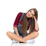 Fille s'asseyant avec des jambes croisées et recherchant Photo stock