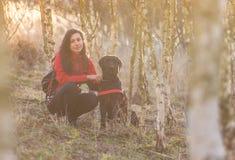 Fille s'asseyant avec le chien dans la forêt de bouleau Photos libres de droits