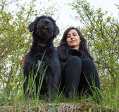 Fille s'asseyant avec le chien sur le pré Images stock
