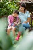 Fille s'asseyant avec le roman de lecture de mère sur le banc en bois Image libre de droits