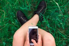 Fille s'asseyant avec le téléphone dans des mains sur la vue supérieure d'herbe photo stock