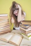 Fille s'asseyant avec un bon nombre de livres et de grippages sa tête Images stock