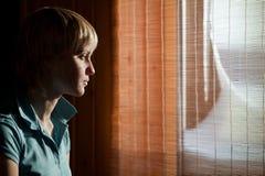 Fille s'asseyant contre une fenêtre Photo stock