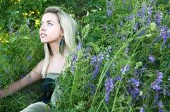 Fille s'asseyant dans l'herbe Photo stock