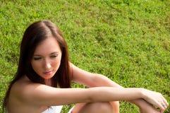 Fille s'asseyant dans l'herbe verte Photographie stock libre de droits