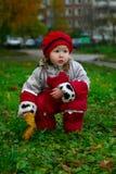 Fille s'asseyant dans l'herbe verte Image stock
