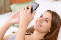 Fille s'asseyant dans l'Internet au téléphone Images libres de droits