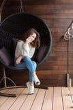 Fille s'asseyant dans la chaise de bulle et parlant au téléphone Photographie stock libre de droits
