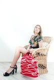 Fille s'asseyant dans la chaise en osier avec le grand sac rouge Photos libres de droits
