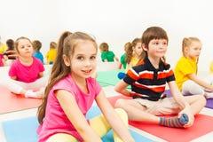 Fille s'asseyant dans la pose de papillon pendant la classe de yoga Photos stock