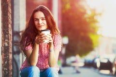 Fille s'asseyant dans la rue avec du café Image stock