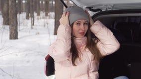 Fille s'asseyant dans la voiture le jour ensoleill? d'hiver, posant pour la cam?ra souriant gentiment clips vidéos