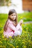Fille s'asseyant dans le domaine des fleurs Image stock
