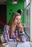 Fille s'asseyant dans un café et une pensée Photographie stock