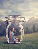 Fille s'asseyant dans un pot en verre Photographie stock
